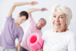 Happy senior woman holding foam mattress, men exercising in background.