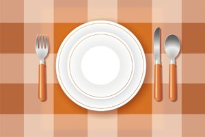 Platos y cubiertos sobre mantel de cuadros naranjas